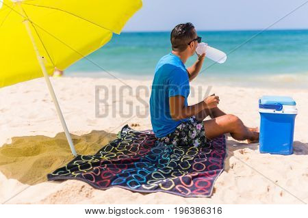 Young Man Under Green Solar Umbrella Drink Water From Cooler On Beach