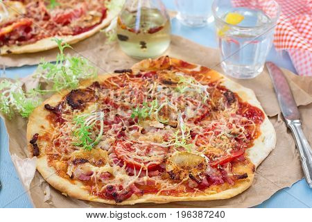 Healthy pizza with thin dough ham lettuce and tomatoes