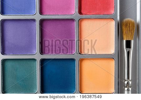 professional cosmetics. Palette of multicolored eye shadow and the makeup brush, top view