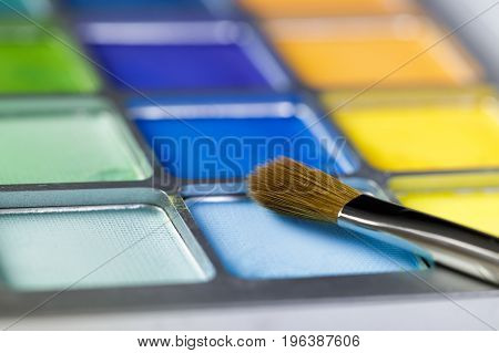 Palette of blue and yellow eye shadow and the makeup brush. Shallow depth of field