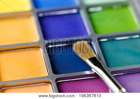 Palette of blue, green and yellow eye shadow and the makeup brush, Shallow depth of field