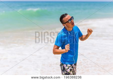 Enjoying Music Sports Lifestyle Happy Young Man In Headphones Walking On The Sea Shore
