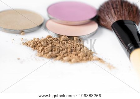 beige powder for face, eye shadow and makeup brush on the white background. Natural makeup