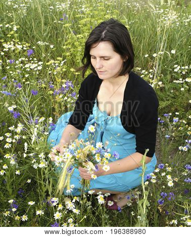 Beautiful girl in the meadow collects wild flowers and have a good time photo for microstock