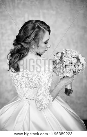 Portrait of beautiful red-haired girl sitting, smiling on big arm-chair. White dress, freckles, red-hair, background, bouquet of flowers.