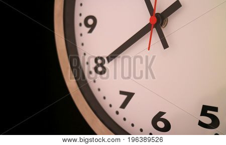 Close-up of round shaped wall clocks at nearly 8 o'clock on black background