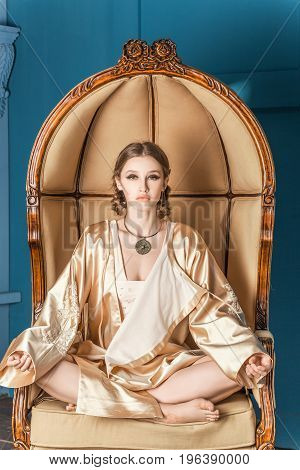 beautiful fashion women exists in oriental style clothing looking at the camera posing on a blue background in a chair