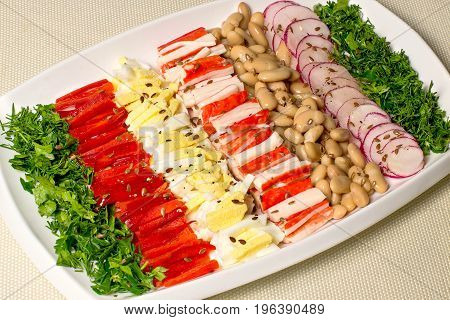Delicious vitamin salad with radish beans sweet pepper eggs surimi and herbs. Salad dressing of oil wine vinegar and seasoning with linseed. Dietary and healthy food