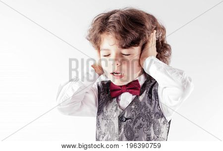 Curly Cute Boy In Waistcoat And Bow Tie Blinked By A Loud Sound And Covered His Ears With His Hands.