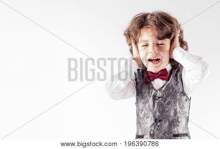 Curly Boy Screaming With Fear Closing Her Eyes And Ears. Gray Background.