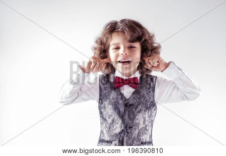 Curly cute boy in waistcoat and bow tie laughing closing ears with your fingers. Close-up. Gray background.