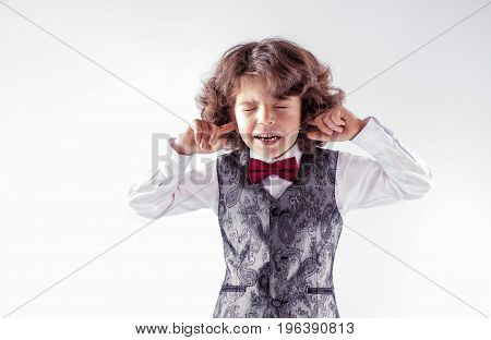 Curly cute boy in waistcoat and bow tie fearfully closed his eyes and ears. Close-up. Gray background.