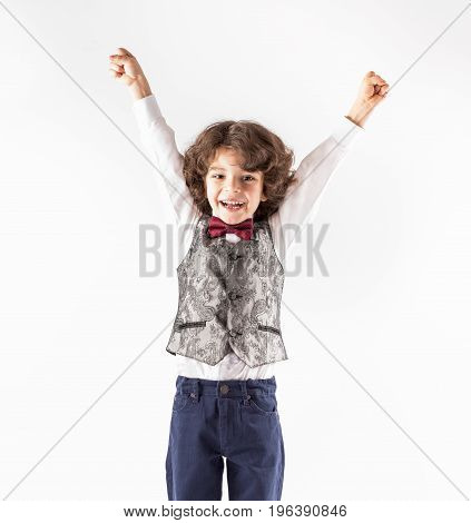 Cute cheerful curly-haired boy in a waistcoat raised his hands with joy. Close-up. Gray background.
