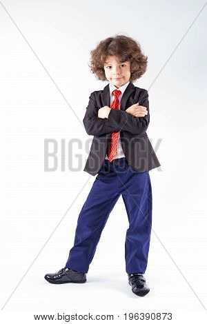Cute curly businessman in an unbuttoned jacket folded his arms and legs apart looking at the camera. Full length. Gray background.