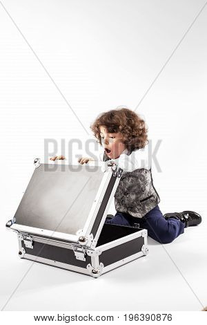 Cute curly little boy sitting on the floor and stares into the open case his mouth open. Gray background.