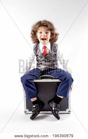 Cute curly little boy sitting on the black briefcase laughing and looking in camera. Gray background.