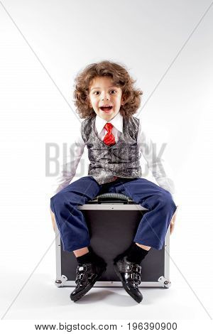 Cute curly little boy sitting on the black briefcase and laughs with his mouth open. Gray background.
