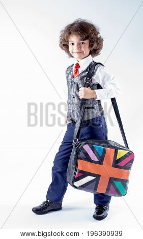 Cute curly boy stands half-turned with a bag over his shoulder. Full height. Gray background.