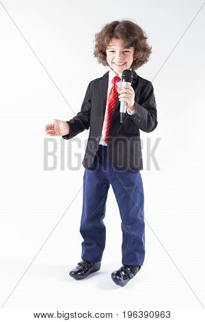 Little Curly-haired Boy With A Microphone In Her Hand Is Smiling And Looking At The Camera. Full Len