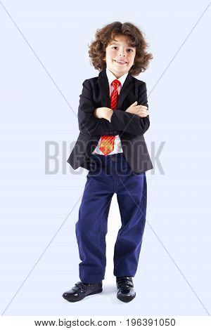 Cute Curly-haired Boy With His Arms Folded Looking At The Camera. Full Length. Gray Background.