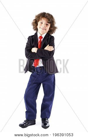 Cute Curly-haired Boy With His Arms Folded Looking At The Camera. Full Length. White Background.