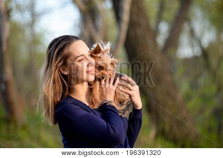 Pretty Young Girl Holds Her Best Friend Little Pet Puppy Of Yorkshire Terrier Breed In Her Arms. Lov