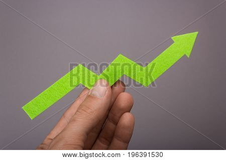 Graph chart growing up in the hand. Success is in your hands. Green arrow up in a man's hand on a gray background. Price increase