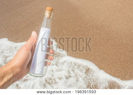 Message in a glass bottle in a man's hand. Sea and waves. Found a note on salvation please help