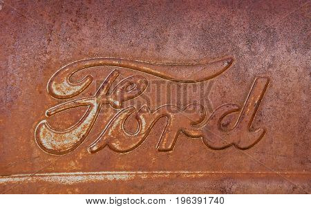 ISABEL, SOUTH DAKOTA, June 22, 2017: The rusty Ford  tractor hood logo is a product of the Ford Motor Company located in Dearborn, Michigan started by Henry Ford and incorporated on June 16, 1903