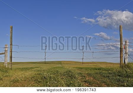 Barren hilly prairie pasture ranch land lies beyond a wire gate