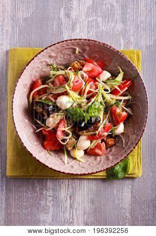 Aubergine mozzarella and tomato warm salad in a bowl