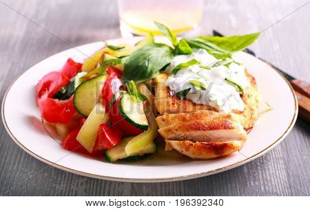 Chicken breast with cream and basil sauce on plate