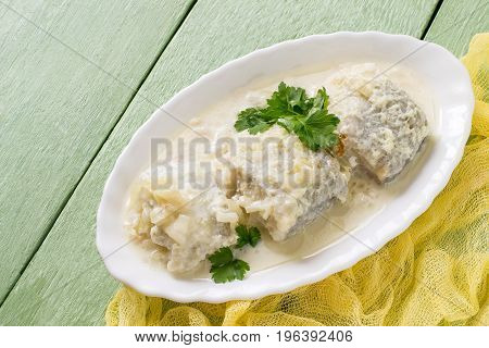 Sea fish stewed in milk-onion sauce. Delicious dietary dish. Served in oval plate on green table with yellow napkin