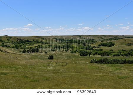 Looking downward unto a prairie valley and a small cemetery and farms