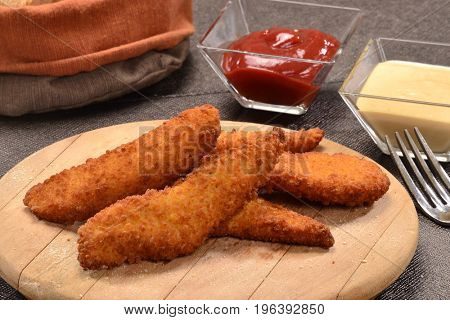 Breaded chicken nuggets breast sticks and sauces.
