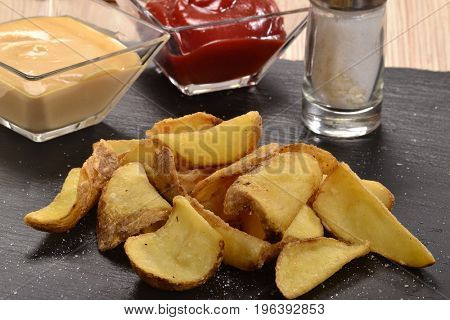 Rustic fried potatoes with shell on stone dish,,ketchup,tartar sauce and salt.