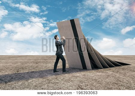 Abstract credit cards falling on businessman in desert. Blue sky background. Debt concept. 3D Rendering
