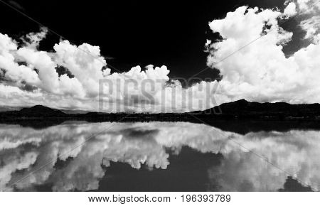 White clouds against the black sky are reflected in the lake. Landscape.