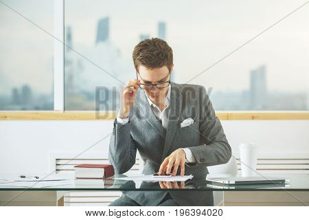 Handsome european man sitting at desk with various items using cellphone and doing paperwork. Blurry city view in the background