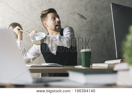 Lunatic businessman about to break computer monitor with lamp while sitting at desk with coffee cup book and other blurry items