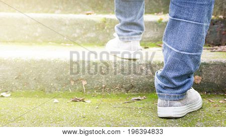 Feet Sneakers And Jeans Walking On Staircase Outdoor With Autumn Season Nature On Background Lifestyle Fashion Trendy Style Walking In The Park Outdoors.