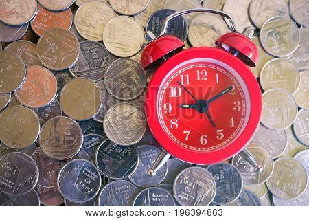 Stack of coins with red fashioned alarm clock for display planning money financial and business accounting concept time is money concept with clock and coins time to work at make money vintage color tone
