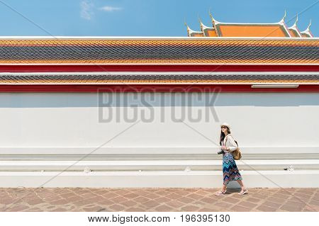 Woman tourist walking in Wat Pho temple Bangkok popular famous location of city travel destination. chinese girl visiting and looking around the sightseeing building architecture.