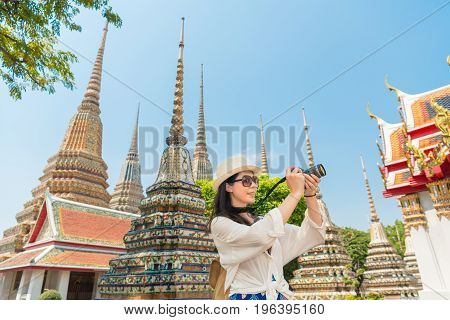 Chinese woman tourist photographer taking pictures with dslr of the wat pho temple Bangkok Thailand. asian girl visiting and looking around the sightseeing building architecture.
