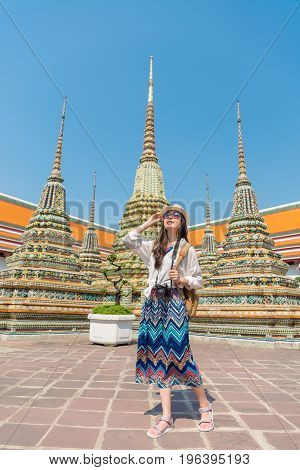 Bangkok City travel - Tourist woman on summer travel looking at sunshine view of wat pho temple with tower building in the background.