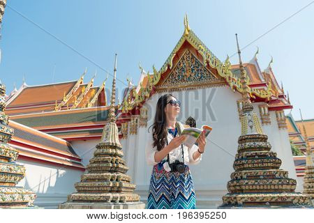 friendly beautiful female traveler holding guidebook reading travel information standing on wat pho temple and looking for route in Bangkok Thailand.