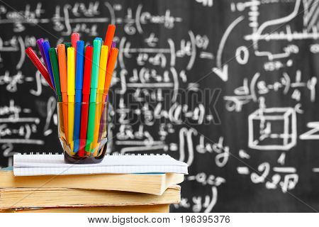 Back to school background with colorful pencils on the books and notebook and the title