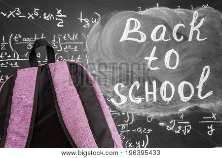 Back to school background with purple school bag and the title