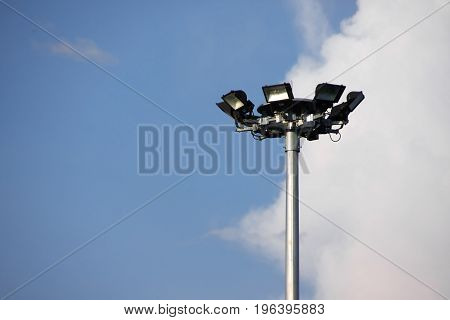 Spot light tower on blue sky with white clound background.
