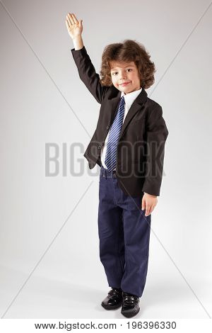 Funny Curly Boy Raised His Hand In A Business Suit, Smiling And Looking At The Camera. Full Length.